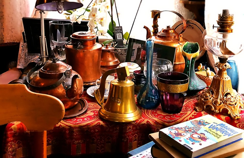 A table full of bric-a brac at the Majorstuen cafe. On a red and gold tablecloth are pots, bells, vases, lamps, glasses, books, plates and a chair in the foreground.