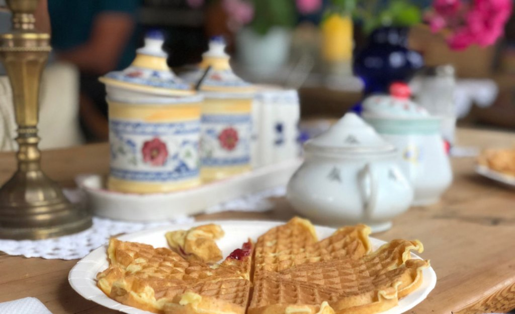 A white plates has a waffle on it that has a slice taken out of. The background is blurry with little yellow, blue white and red pots in the background.