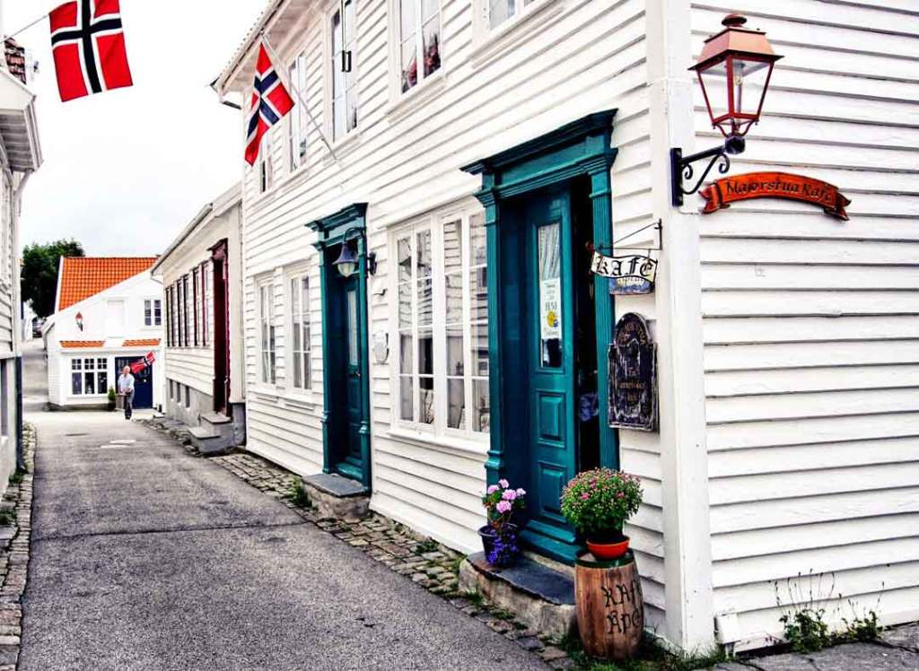 A white wooden house with a green door, the entrance to Majorstuen Kafe. Norwegian flags hang on the outside and a lamp is on the side of the house