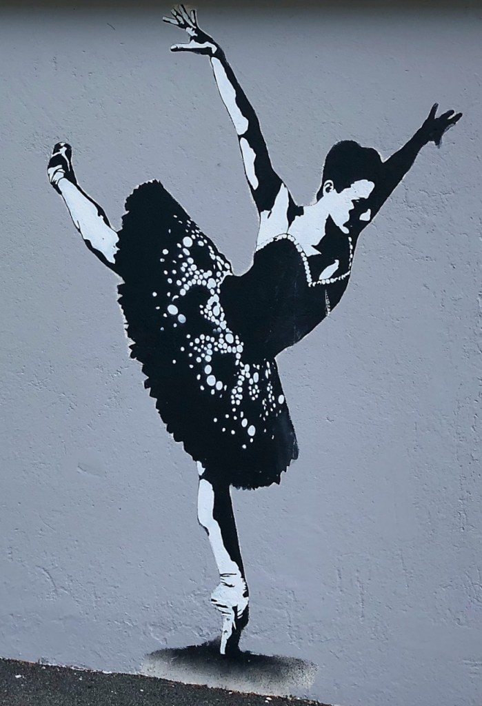 Street art of a black and white ballerina on the side of a house