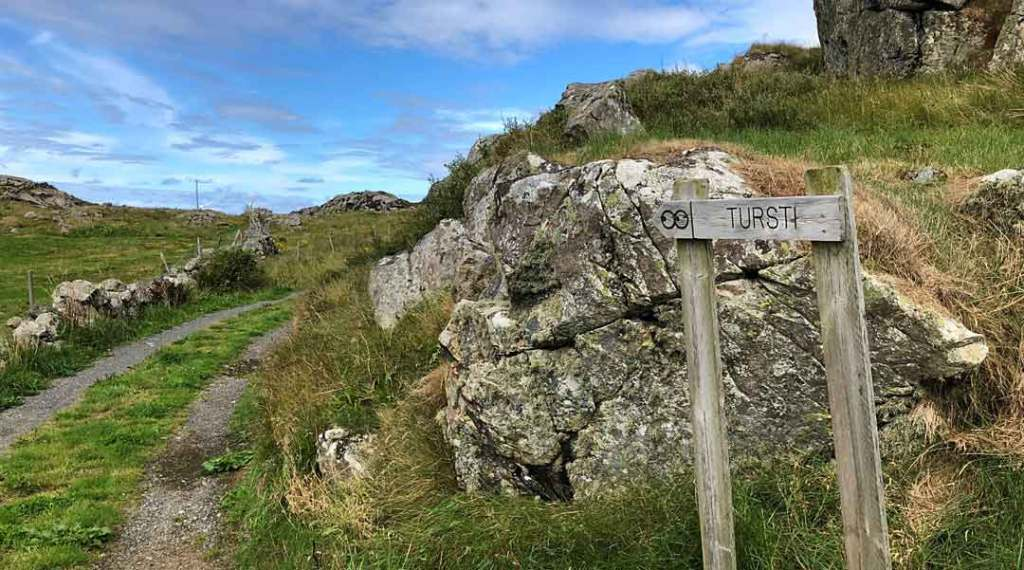 A wooden sign that says 'Turisti' and a path leading around the rock and green field.
