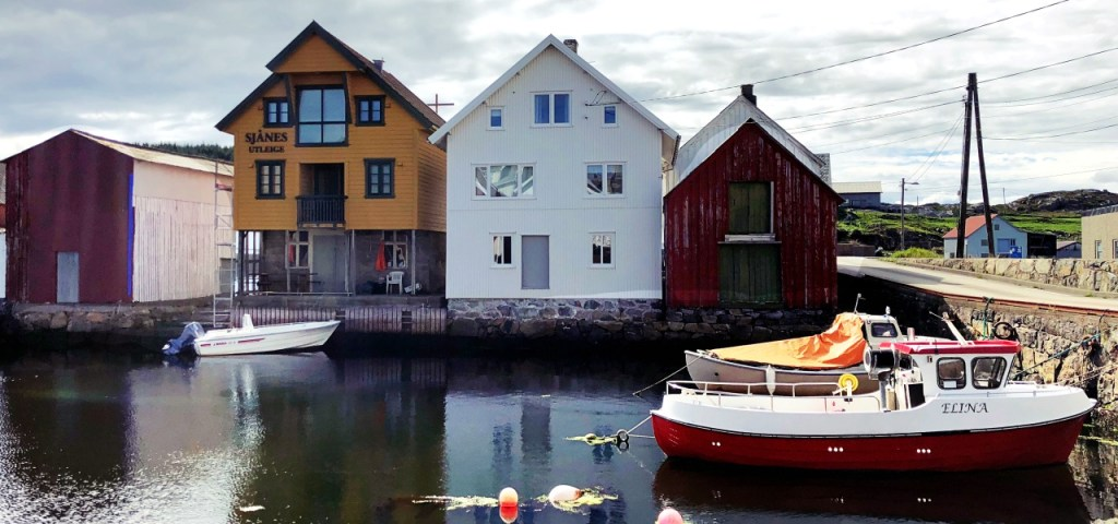 North harbour with a yellow, white and red hut beside the harbour wharf. A red and white boat is in the foreground.