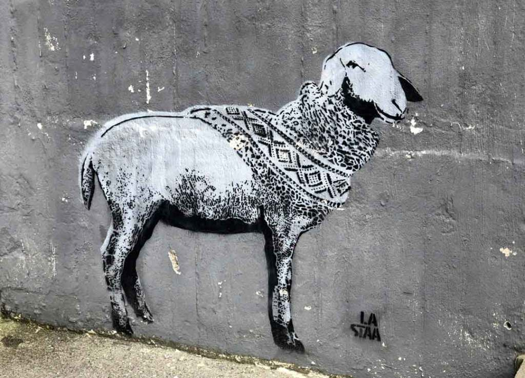 street art of sheep wearing a scarf with a criss cross pattern on it