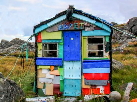 A multi-coloured hut made of plastic from the sea near the ocean. Grass and rocks in the background