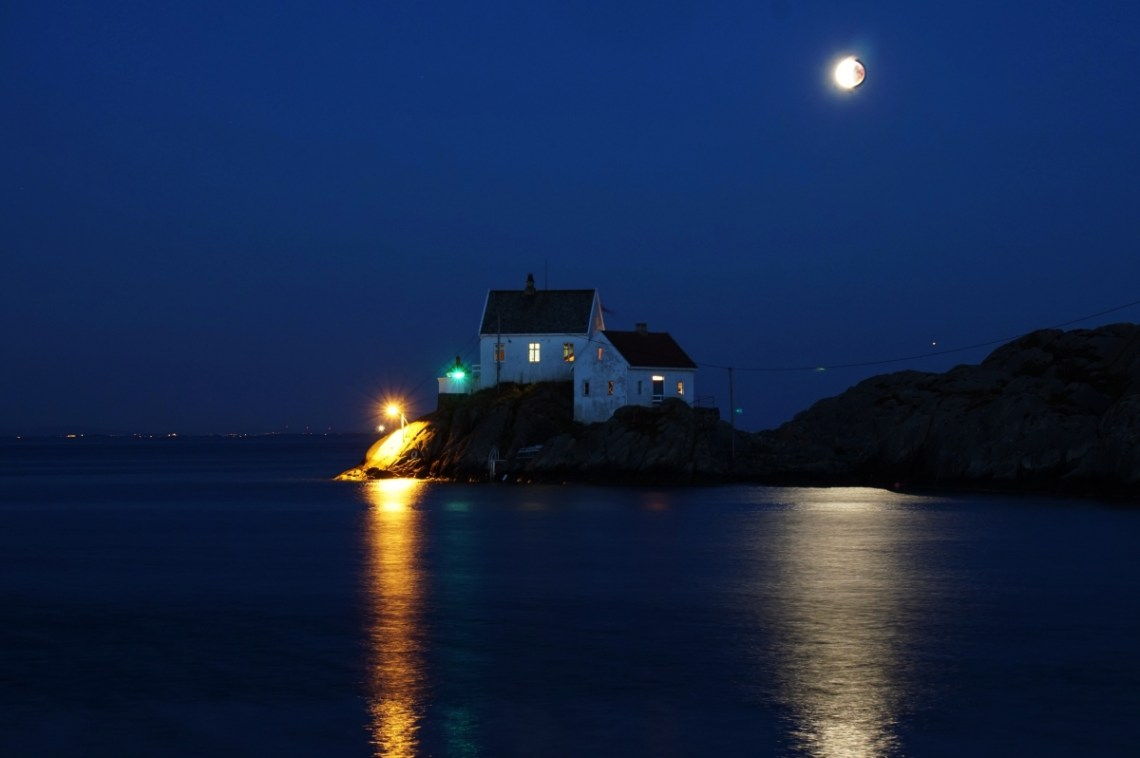 A bright moon at the end of an eclipse, still slightly in shadow, overhead of two white houses beside a small lighthouse on rocks surrounded by ocean.