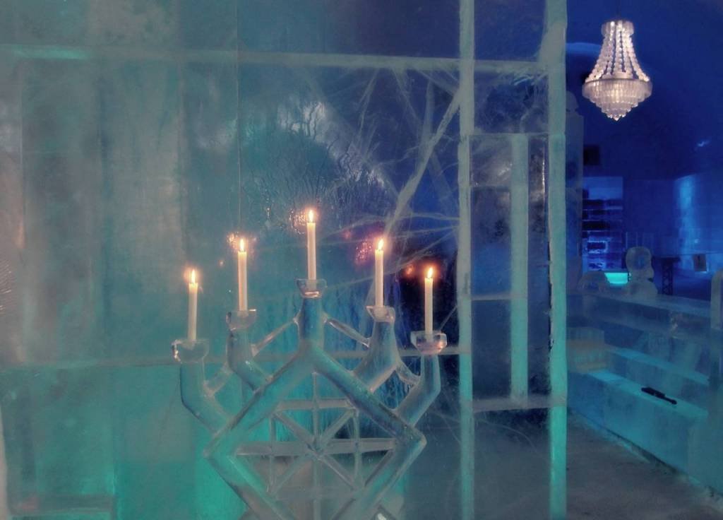 In the main hall of the 365 ice hotel - An ice candelabra in the forground with 5 candles. In the background on the ceiling is an ice chandelier.