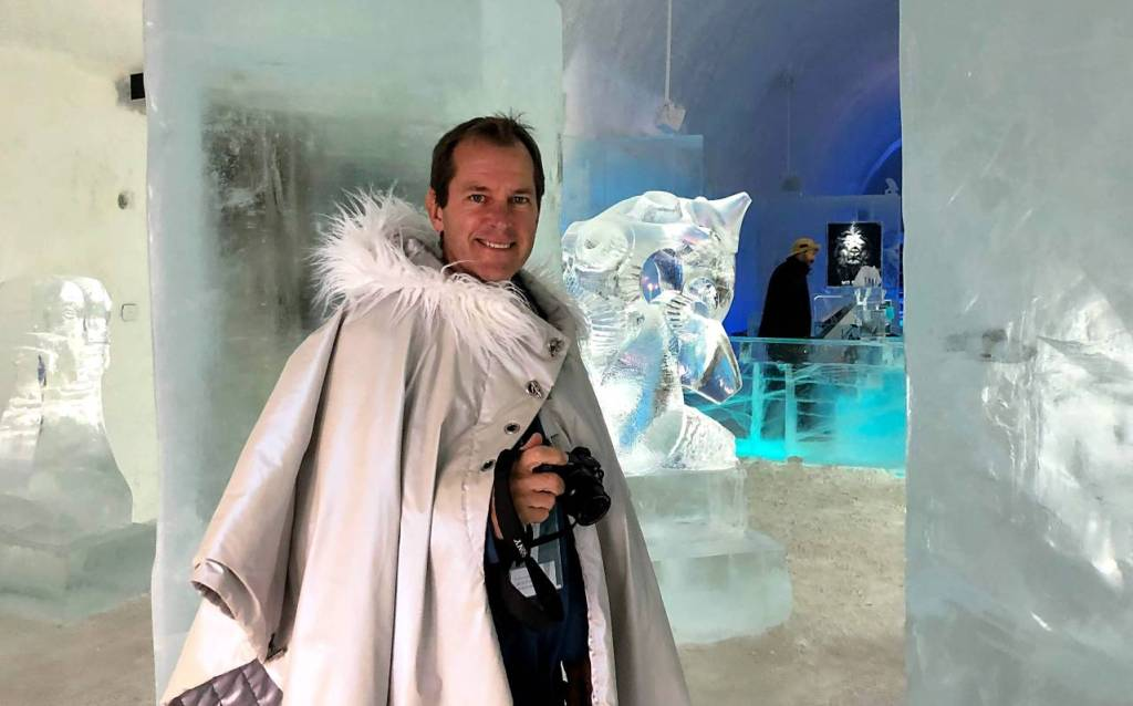 Lars, wearing a stone coloured lined thick cape with furry collar. The ice sculptures in the background.