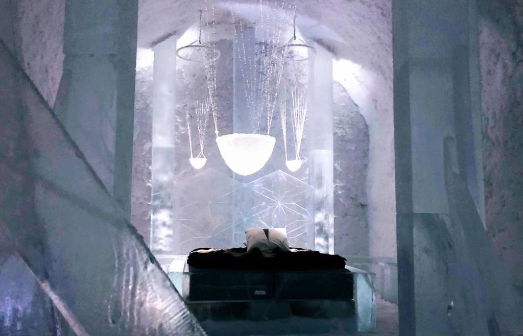 A zigzag headboard of ice behind the bed and ice crystal chandeliers hanging over the bed