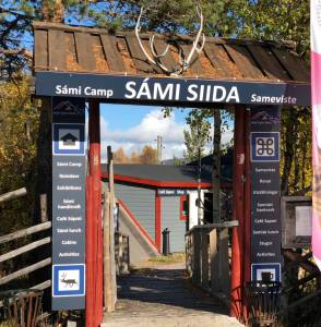The entrance to Nutti Sami Siida, a rectangular doorway witout doors and a wooden tilted roof. Either side there are grey signs higlighting waht is inside, eg cafe activities, etc.