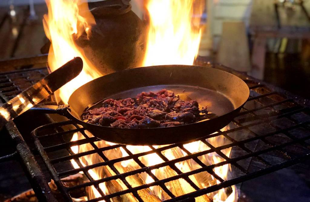 A frying pan with the sliced smoked reindeer meat sizzling in the pan over the open fire.