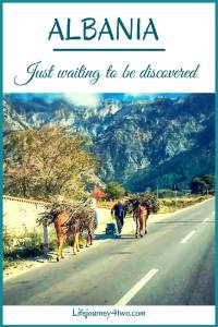 Pinterest pin Albania -Just waiting to be discovered Photo of road with Two horses with sticks on their backs. Mountains in the background.