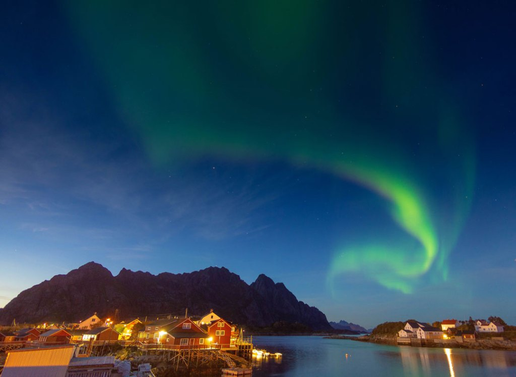 Green swirling northern lights over a bay with mountain backdrop