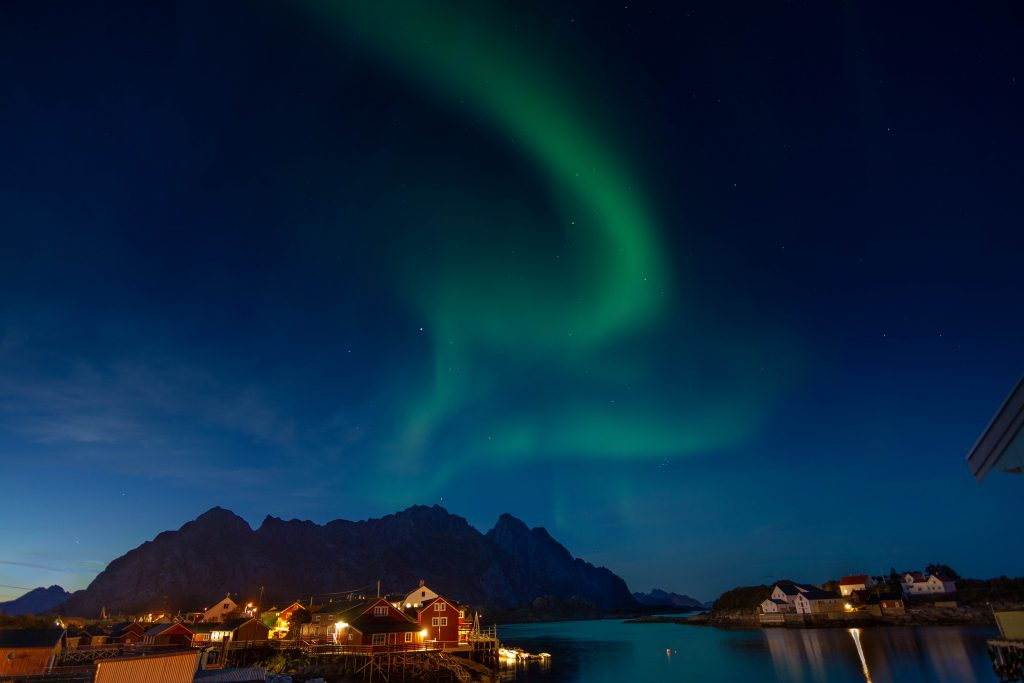 Green swirling northern lights over a dark mountain range with a yellowish hued town in the foreground