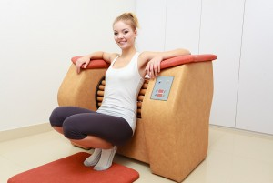 Smiling blond girl in sportwear using modern relax massage equipment. Young woman doing relaxation exercise in healthy spa salon.