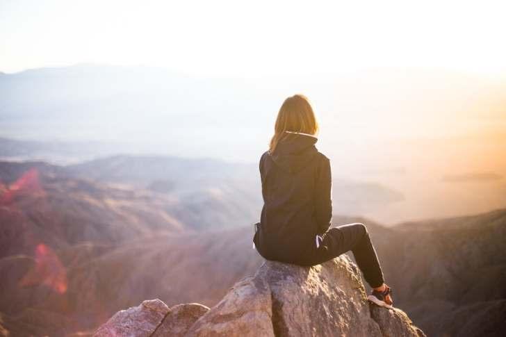 山の山頂に女性が腰を下ろす