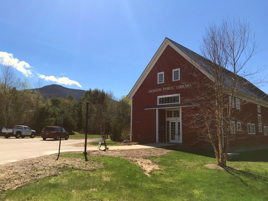 The Jackson Public Library in Jackson, NH pictured with mountains in the background.