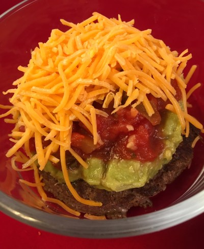 cooked hamburger patty topped with guacamole, salsa, and shredded cheddar cheese