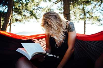 woman reading a book in outdoor setting