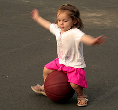 Little girl trying to balance on a ball (Photo by Sharon Mollerus on Flickr)