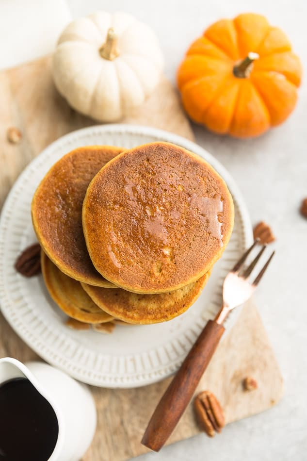 Top view of 4 fluffy fluffy low carb pumpkin pancakes on a white plate with a copper fork