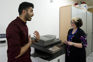 Colleagues chat at a photocopier.
