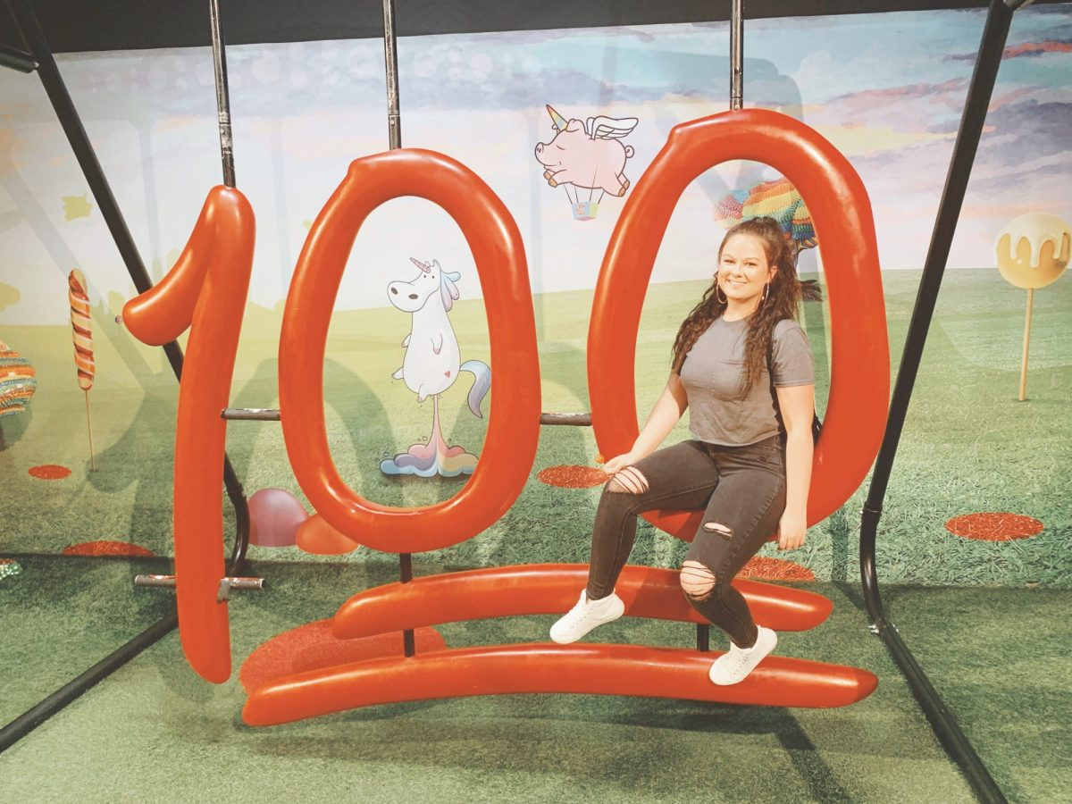 Becca G sitting on a big 100 sign at Candytopia in a grey shirt and black jeans