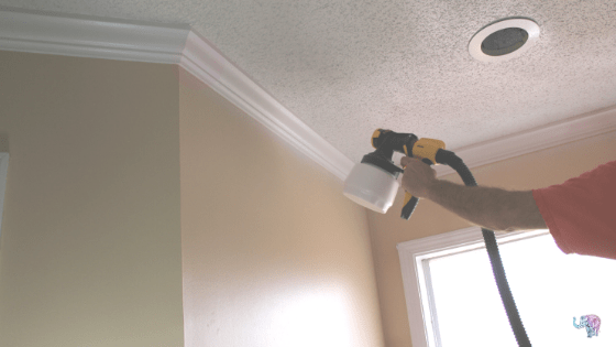 Using  paint sprayer to paint ceiling.