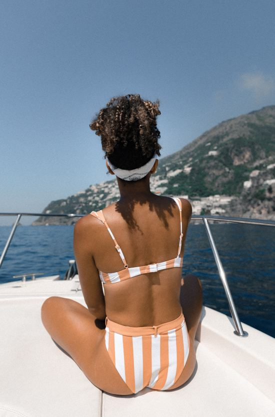 Lady on a boat in a swimsuit.
