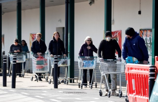 Shoppers, with trolleys, queuing outside a shop and maintaining social distance