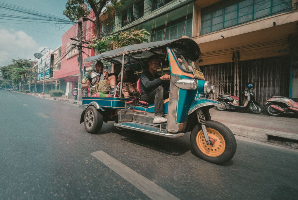 three people on a tuk tuk in asia