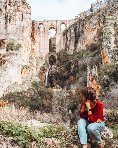 Girl sitting in front the bridge in Ronda, Spain. Puente Nuevo