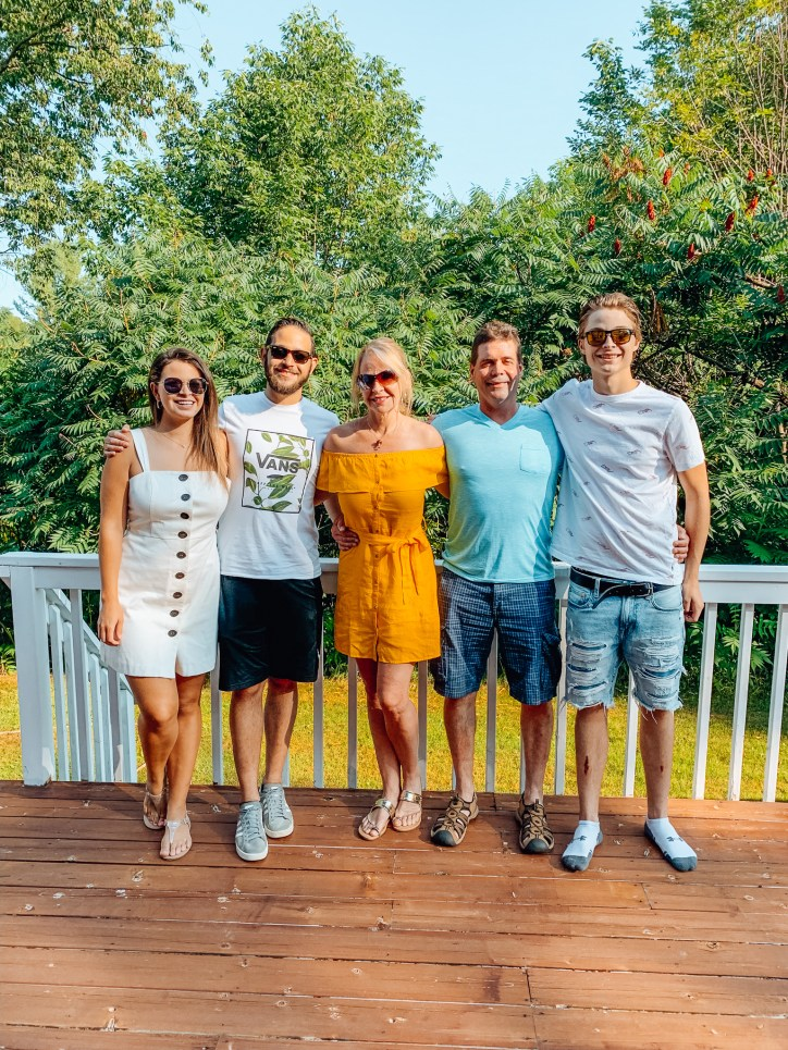 Five people standing in front of a railing
