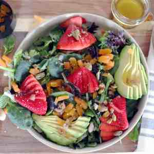 Strawberry, Apricot, Pistachio Salad with avocado and dressing photographed top down