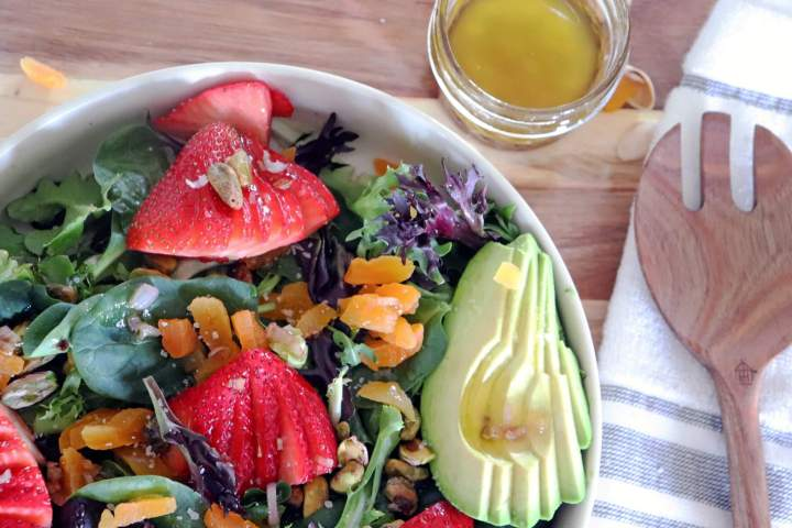 Spring Salad Mix Recipe - half bowl of finished salad, dressing in a jar and a tossing spoon on a napkin.