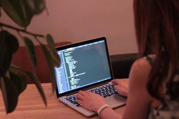 おしゃれなカフェでMBPを使い仕事をする女の子のフリー写真素材