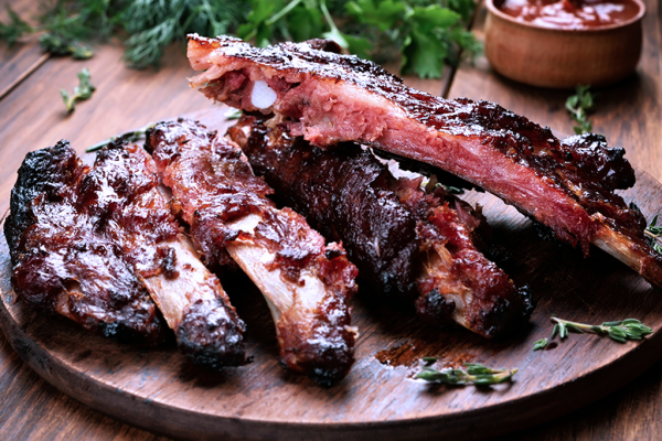 Plate of cooked pork ribs with barbecue sauce