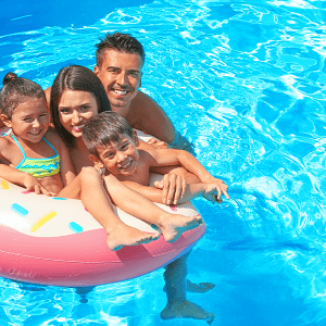 Family relaxing in pool summer getaway