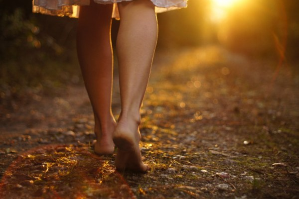 Young female legs walking towards the sunset on a dirt road