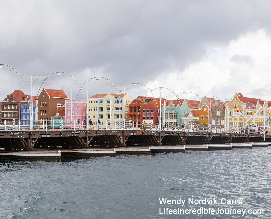 Colourful buildings and Queen Emma Pontoon swing bridge at UNESCO World Heritage Site of Willemstad on the Caribbean Island of Curaçao. The waterfront market at the UNESCO World Heritage Site of Willemstad on the Caribbean Island of Curaçao. Photo Credit: Wendy Nordvik-Carr