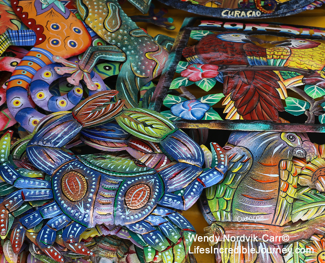 Colourful artwork at the waterfront market at the UNESCO World Heritage Site of Willemstad on the Caribbean Island of Curaçao. The waterfront market at the UNESCO World Heritage Site of Willemstad on the Caribbean Island of Curaçao. Photo Credit: Wendy Nordvik-Carr