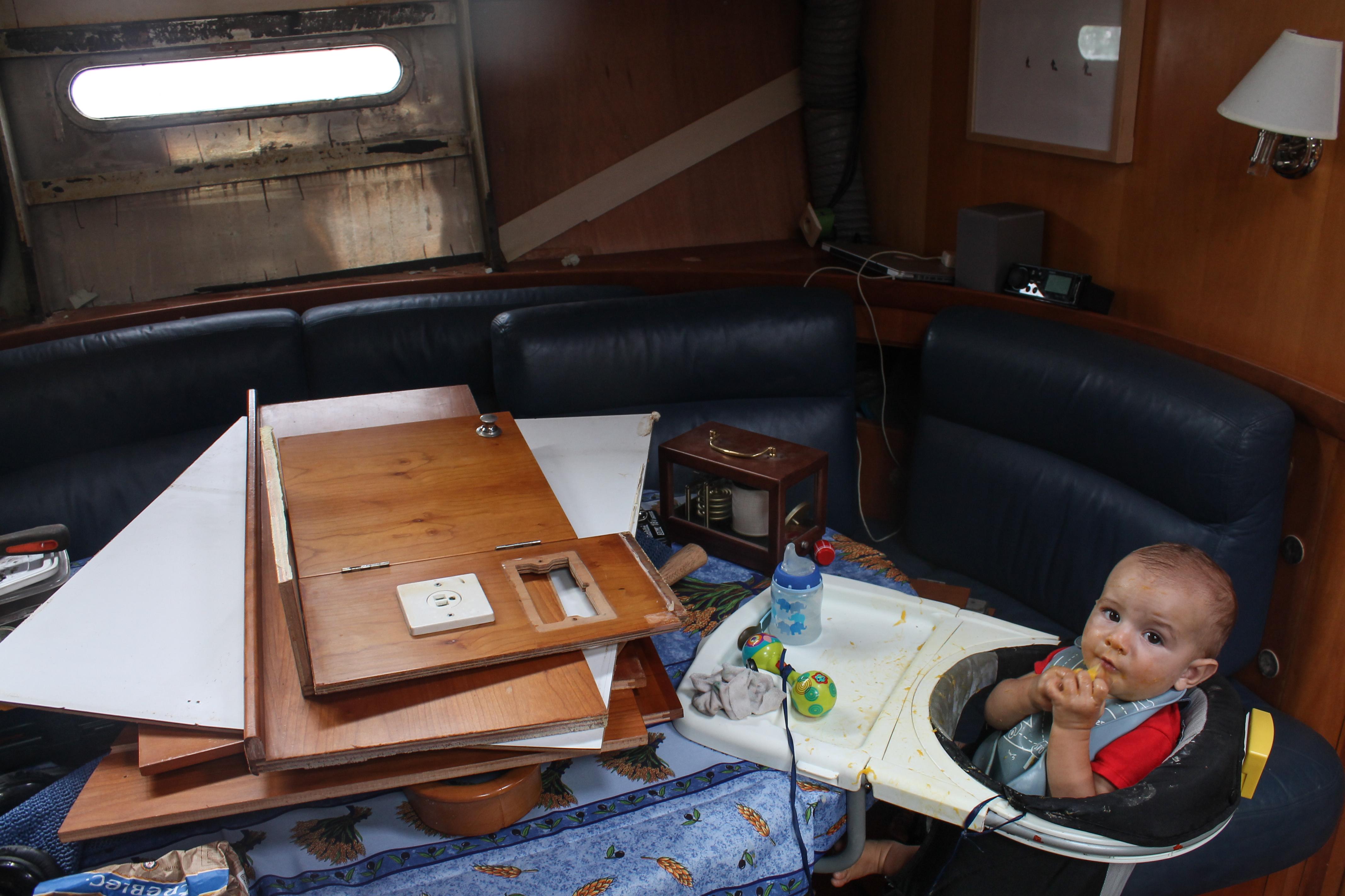 Raphael mange dans le bateau entouré de miles objets