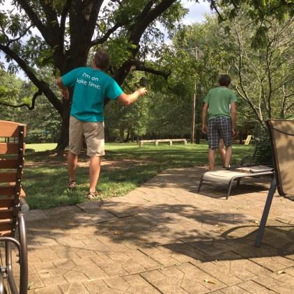 Dad shows Sam how to throw walnuts