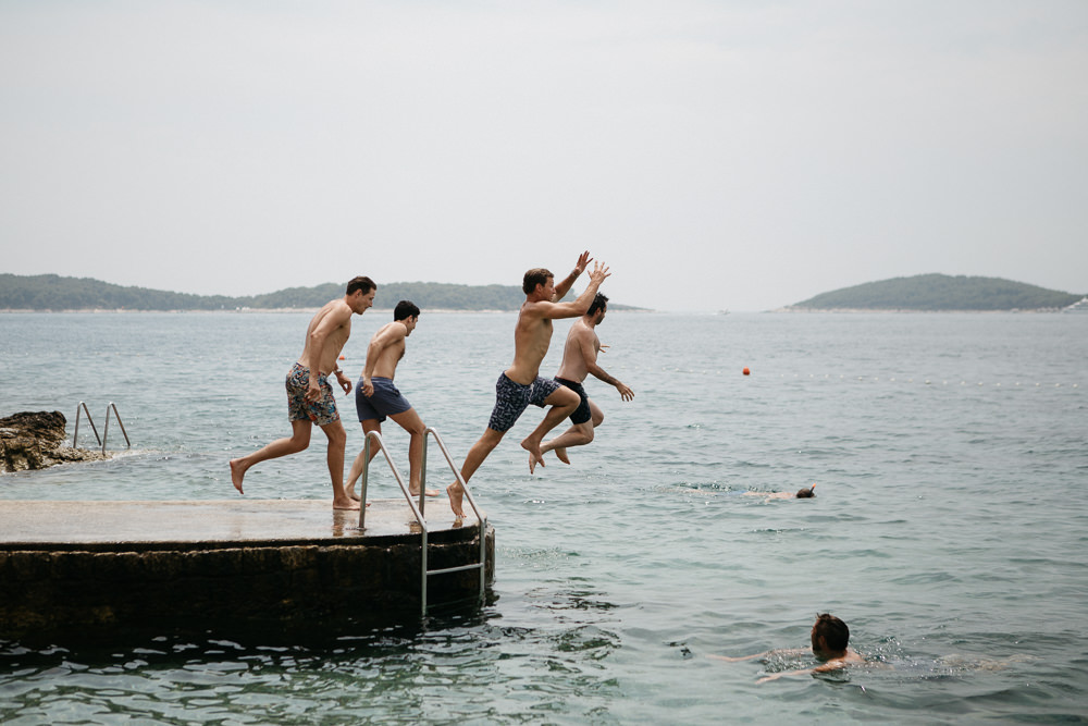 groom and groomsmen jumping in the water on a wedding day in Hvar Croatia