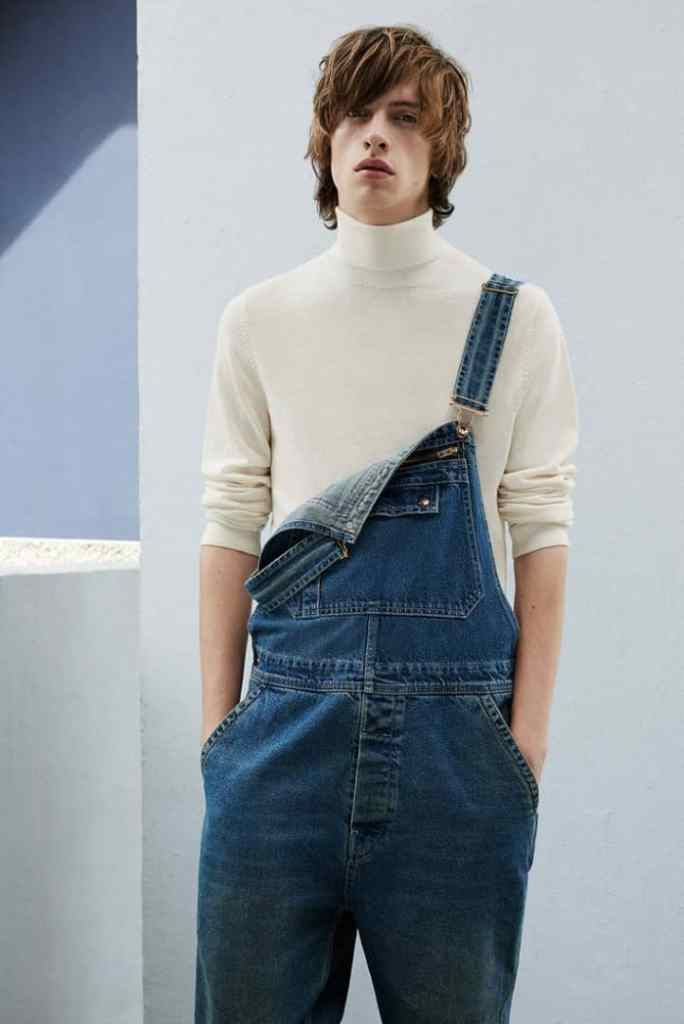 A man wearing white turtleneck with jeans dungaree