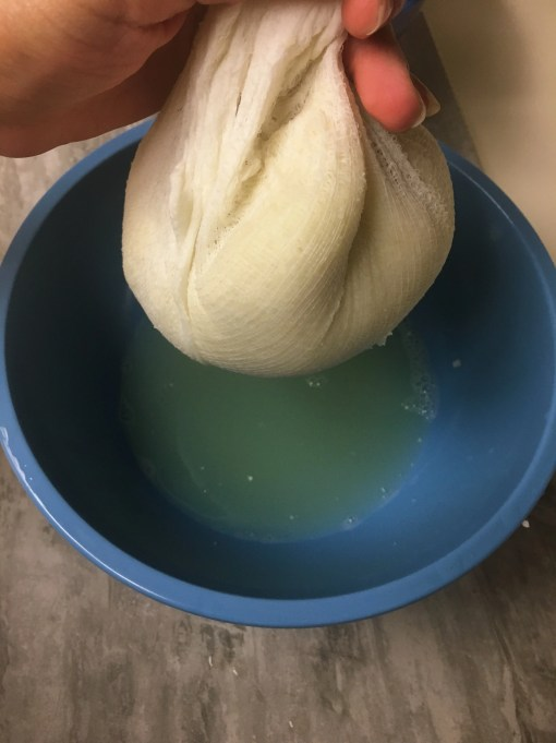cauliflower being drained by a cheese cloth for the making of a delicious no carb pizza crust