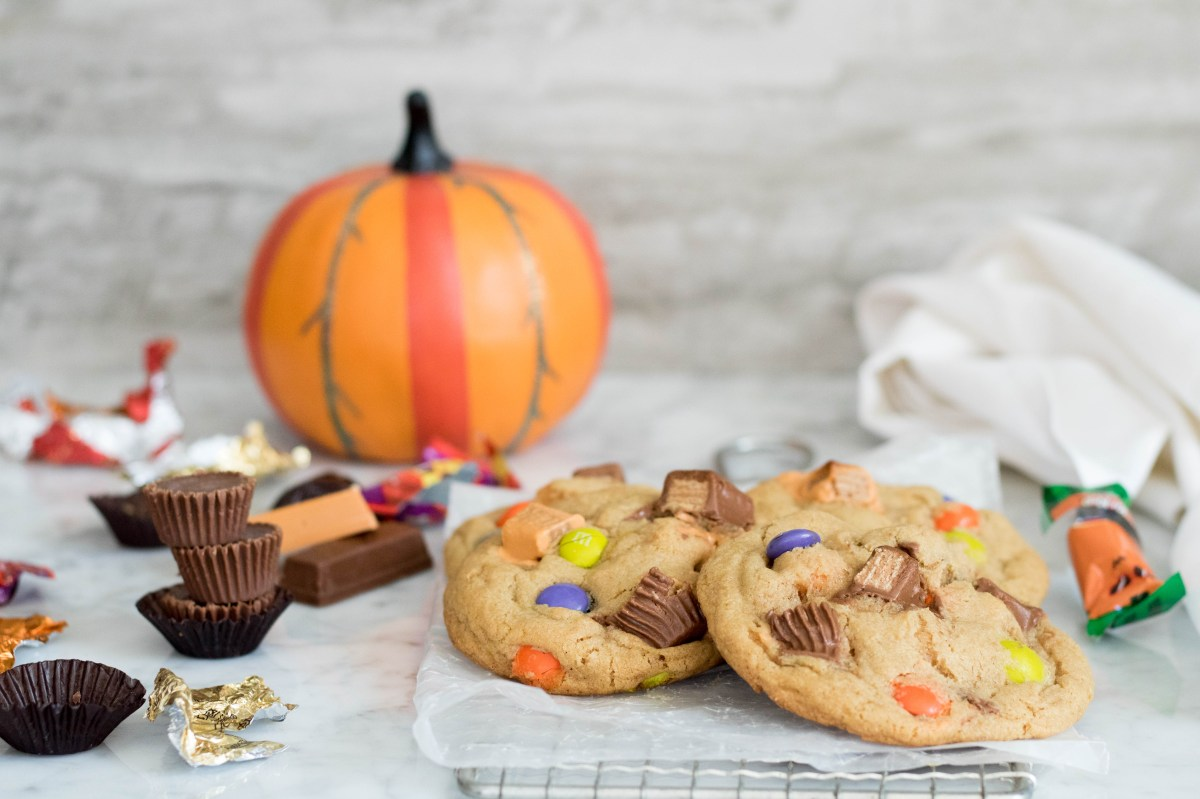 2 large halloween cookies with lots of different leftover chocolate and candies