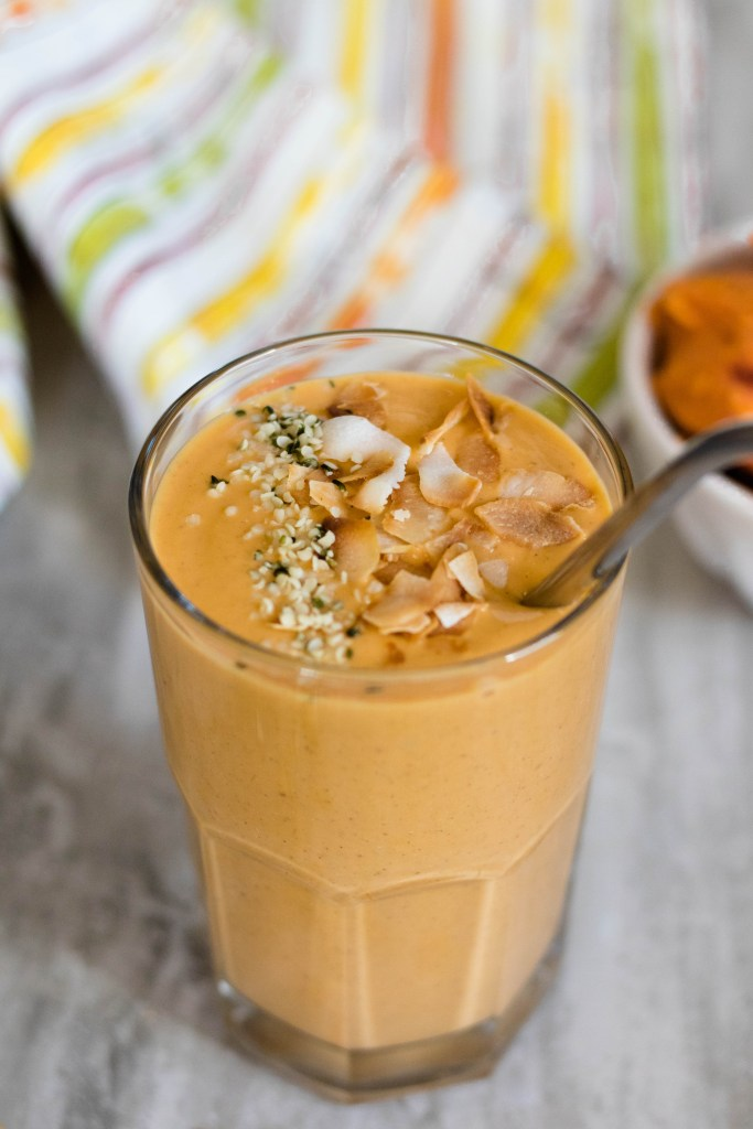 Sweet potato in smoothie in a tall glass with a metal straw