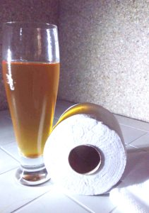 Urine-colored iced tea in a glass with a rolled toilet paper