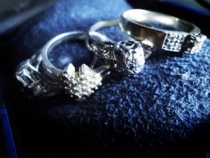 Four examples of generation engagement rings, antique and of varied shapes and sizes.