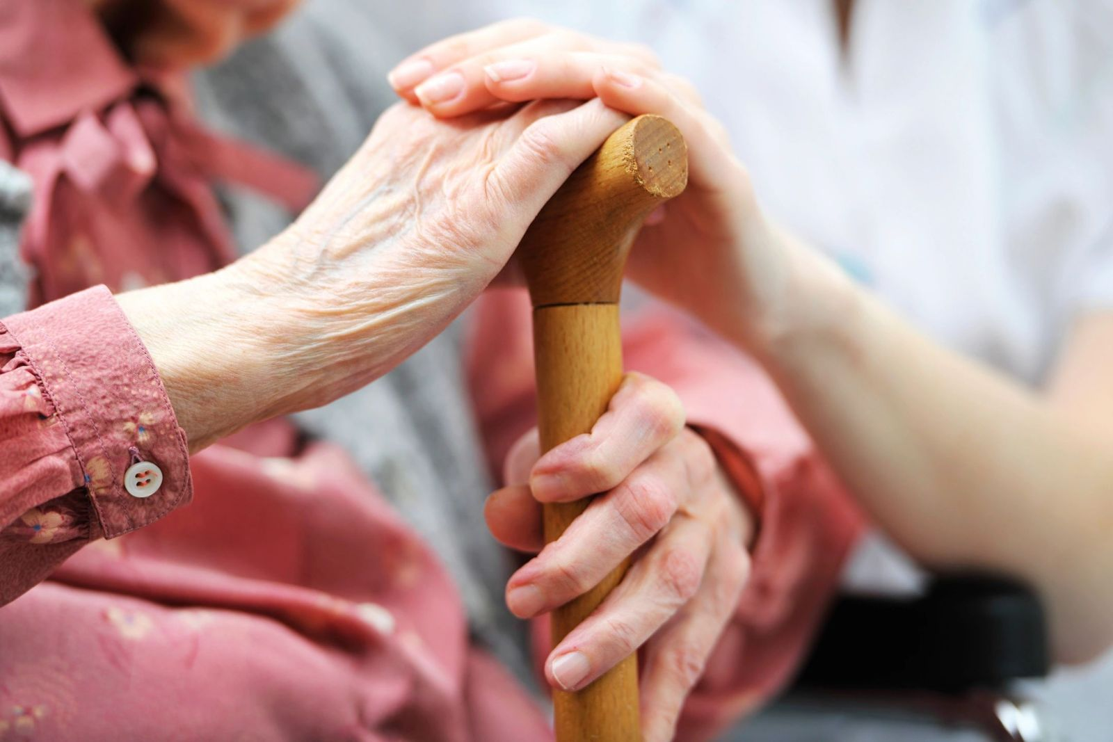 Senior holding a walking stick and another person helping